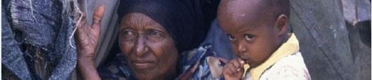 Eine Frau und ein Kind warten vor einer Hütte in Somalia